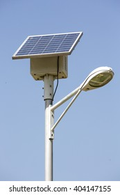Single street lamp above an alley in the park. A lamp with its own solar panel which collects the energy from the light for the evening.
