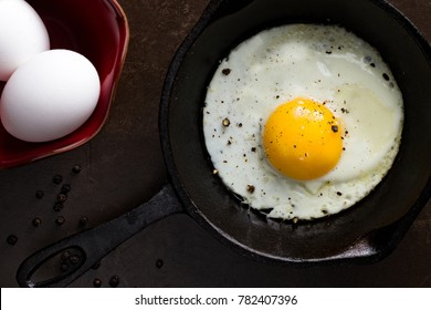 A single sunny side up egg in a cast iron skillet