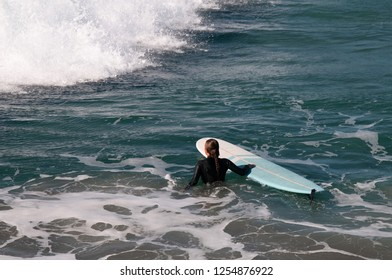A single surfer wades as they wait for the next big wave on the pacific coastline in Oceanside California
