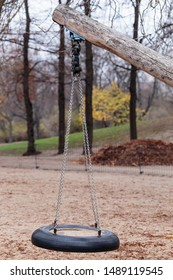 A single swing made out of chains and a tire hangs from a wooden trunk in an empty playground, in a public park in Berlin, on a grey and cold autumn afternoon. Vertical detail view, absence concept.