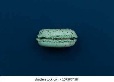 Single Teal Blue Macaroon Cookie on its Side Against a Navy Blue Background Shot From Above