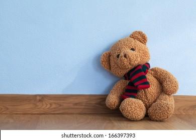 Single teddy bear on a floor in a child room