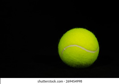 A single tennis ball against a solid black background.