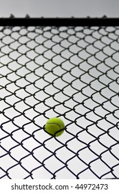 A single tennis ball stuck in the fence at a tennis court, with an overcast sky in behind.