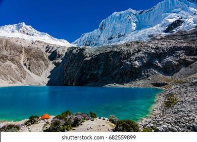 Single tent pitched at wonderful mountain lake Laguna 69 in Peru