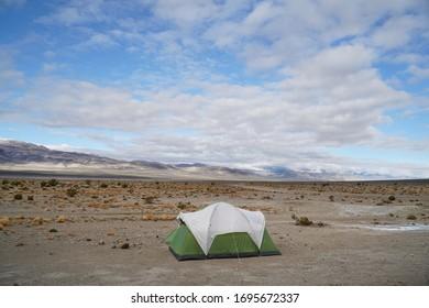 A single tent sits in a vast desert landscape.