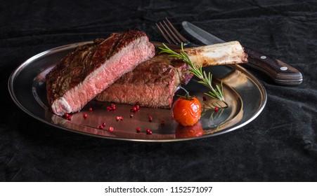 Single tomahawk rib steak on silver dish next to roasted cherry