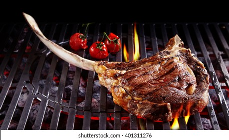 Single tomahawk rib steak on hot black grill next to three roasted cherry tomatoes with flames underneath