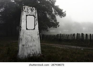 A single tombstone near a foggy road