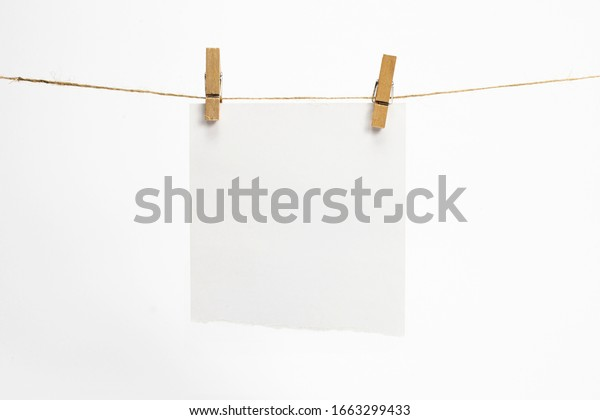 Single torned paper sheet for notes that hang on a rope with clothespins and isolated on white. Blank white cards on rope mockup template.