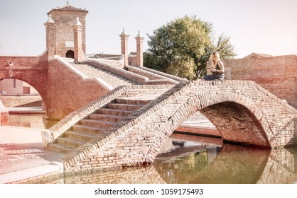 single tourist woman in italy sitting on treponti bridge in comacchio medieval town of italy