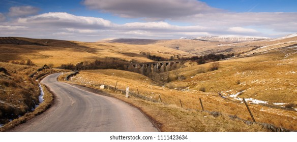 A single track country lane climbs from Dentdale above the Dent Head Viaduct on the Settle-Carlisle Railway Line in the rolling moorland landscape of the Yorkshire Dales National Park.