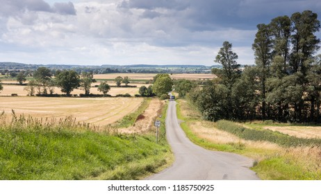 A single track country lane runs through fields of crops and pasture at Tansor Wold near Oundle in Northamptonshire's Nene Valley.