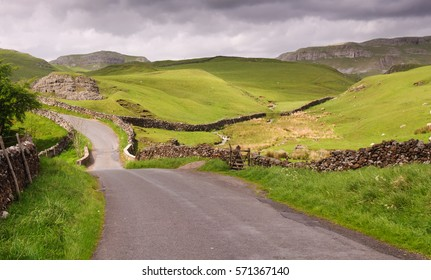 A single track country lane runs through the limestone karst landscape of England's Yorkshire Dales National Park.