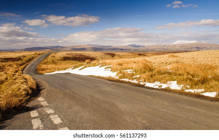 A single track country road crossing high moorland in the remote Forest of Bowland uplands in Lancashire, England.