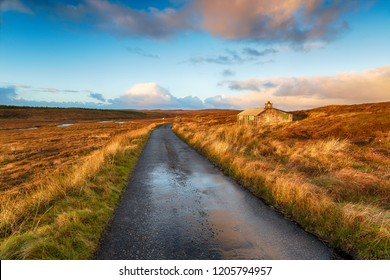 A single track road over a peat bog and past a shieling hut near Stornoway on the Isle of Lewis in the Outer Hebrides in Scotland