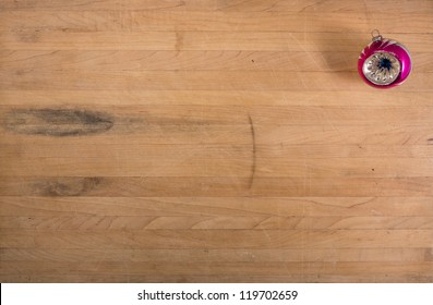 A single traditional glass ornament sits on a butcher block countertop