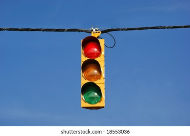 Single traffic light against blue sky background.