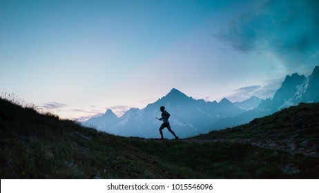 A single trail runner, silhouetted against the sky at sunrise while running in the mountains of the Alps along a steep trail