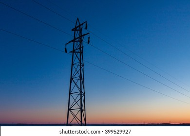 A single transmission tower stands against a quiet prairie sunset.