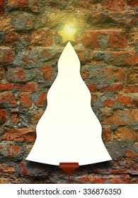 Single tree shaped frame with turned on star on brick wall background