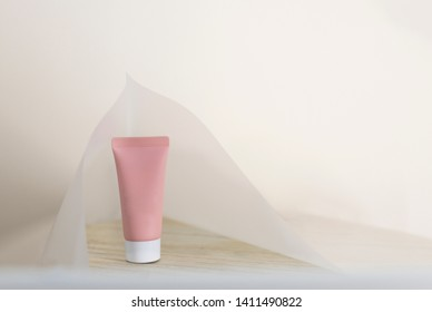 Single tube of cosmetic product on wooden surface covered with white paper on pale background. Rose skin care cream. Copy space and design space. Take care of yourself. Beauty ritual concept.