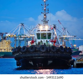 A single tugboat with massive tires fastened to the hull at evening time
