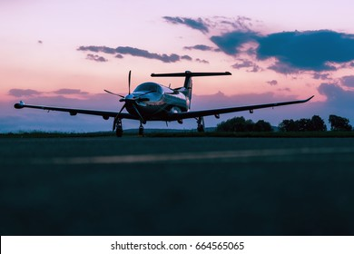 Single turboprop aircraft on evening runway after sunset-