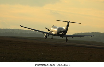 Single turboprop airplane taking off from airport.