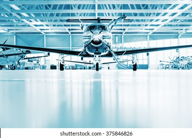 Single turboprop business aircraft  in hangar, blue colored