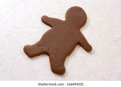 Single uncooked gingerbread man shape in cookie dough