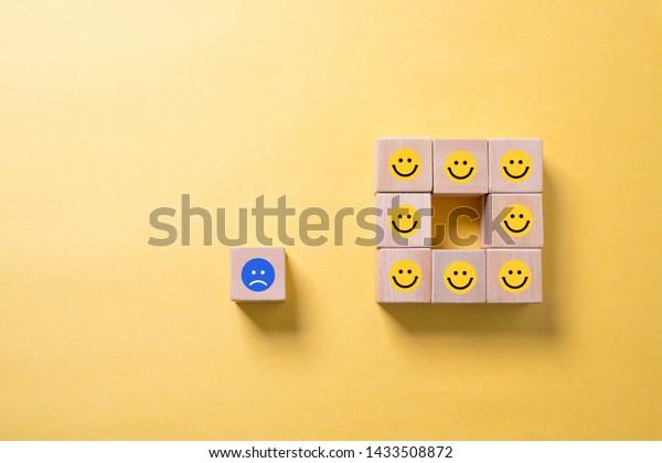 Single unhappy block and group of happy blocks symbolizing feeling lonely over illuminated orange background