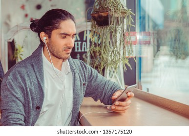 Single unhappy man with earphones, person looking to a mobile phone. Closeup portrait of a handsome guy wearing formal white shirt and gray blouse sitting near window at a table in living room.