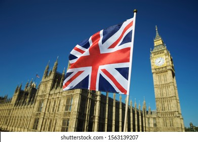 Single Union Jack flag waving in front of Big Ben at the Houses of Parliament in London, UK on a clear sunny day