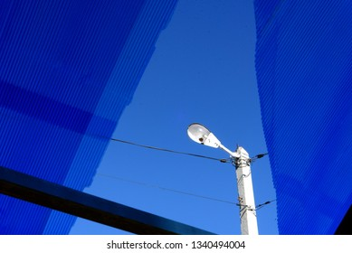 Single urban streetlight during the day through cracked blue Acrylic Perspex and blue sky
