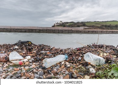 Single use plastic bottles and other plastics washed up on shingle beach of River Cuckmere estuary