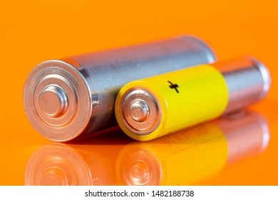 Single used AA and single AAA alkaline battery are seen on a reflective orange surface. Closeup side view from the plus side of the batteries.