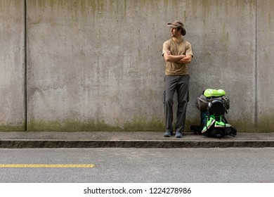 A single white adult man with a packed backpack standing on the roadside in front of a gray wall hitchhiking