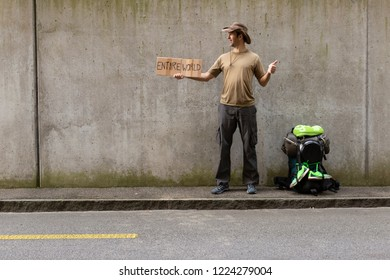 A single white adult man with a packed backpack standing on the roadside in front of a gray wall hitchhiking with outstretched thumb and a cardboard sign reading entire world
