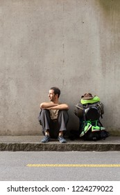 A single white adult man with a packed backpack sitting on the roadside in front of a gray wall taking a break from hitchhiking