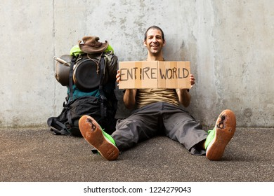A single white adult man with a packed backpack sitting on the roadside in front of a gray wall wearing broken green shoes and holding a cardboard sign reading entire world
