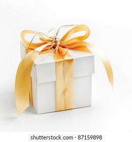 Single white gift box tied with gold ribbon on white background.