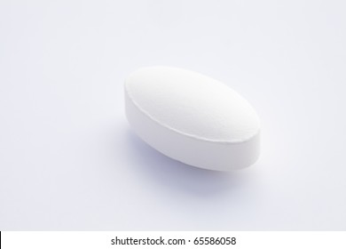 single white oval tablet on white background