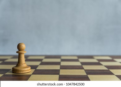 A single white pawn on the chessboard