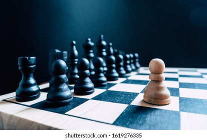 A single white pawn stands against an entire board of black chess pieces. Representative of a one man army/business leader standing against the competition - with room for text