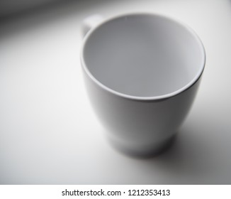 Single White porcelain or ceramic mug isolated on a plain background
