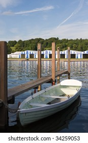A single white rowing boat on the river in Henley-on-Thames, England, with regatta tents in background