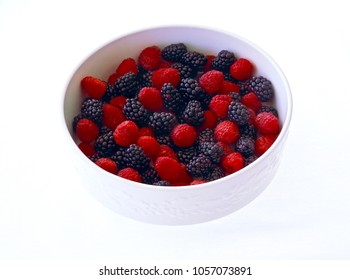 Single white serving bowl with bright red raspberries and blackberries.