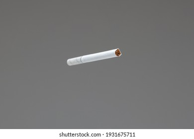 Single white unlit cigarette close up macro studio shot isolated on gray background shallow depth of field.