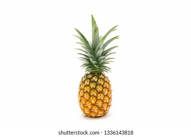 Single whole pineapple with green leaves isolated on white background.